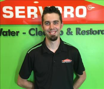 Male employee in black SERVPRO shirt in front of a green background with orange SERVPRO logo