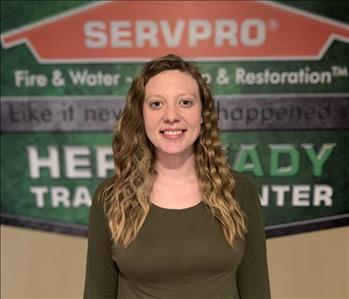 Female employee with curly hair standing in front of a SERVPRO wall. She is wearing a green shirt