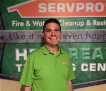 Male employee in green SERVPRO shirt standing in front of a SERVPRO wall