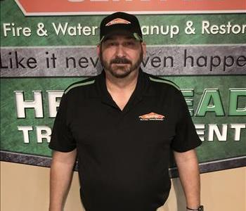 male employee standing in front of a green SERVPRO wall while wearing a black SERVPRO shirt and hat