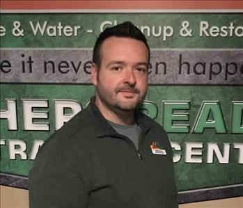 Male employee wearing a green long sleeve shirt with SERVPRO logo on the wall behind him