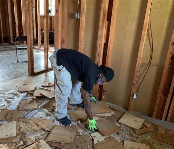African American man working to clean up in a room with wood covering the floor. Drywall is gone from walls