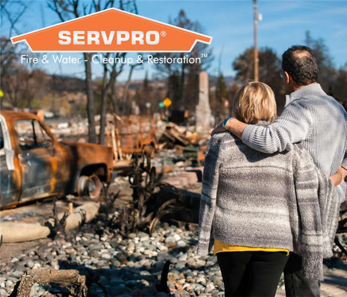 Man and woman standing facing away from the camera while looking at a destroyed area where there used to be a home