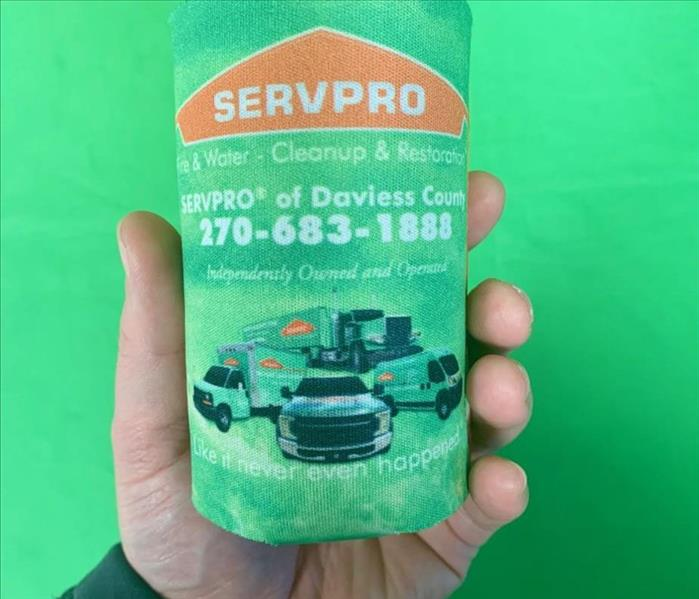 Hand holding up a can with a SERVPRO koozie on it