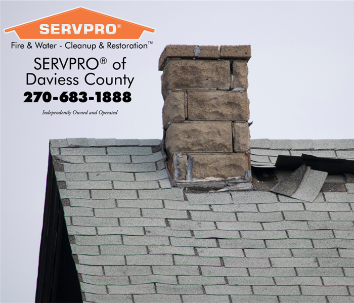 Roof with messed up shingles, and a chimney. SERVPRO logo in upper left corner of photo