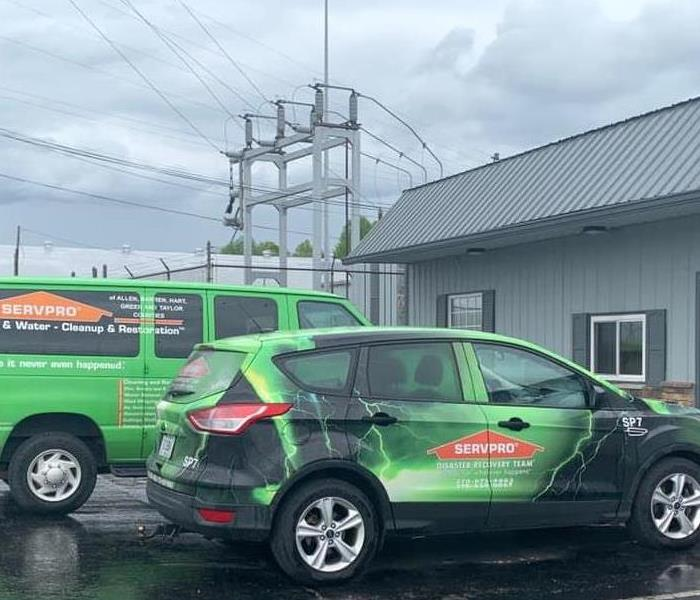 SERVPRO van and SUV parked in front of a local business